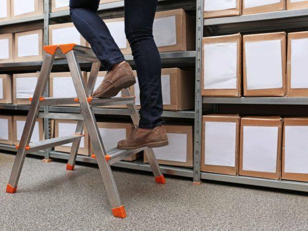 mann steigt auf die Leiter und szeigt den richtigen Umgang mit Leitern