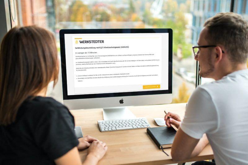 Zwei Kollegen die eine Gefährdungsbeurteilung online erstellen
